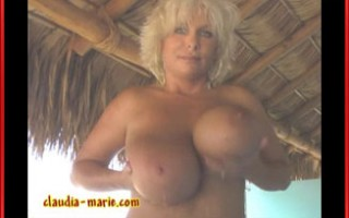 Claudia-Marie plays with her giant tits while smoking a cigar.