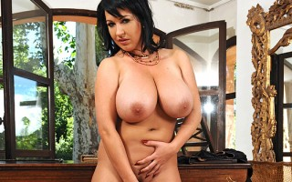 Raven haired big titty Kora and a happy orange dildo