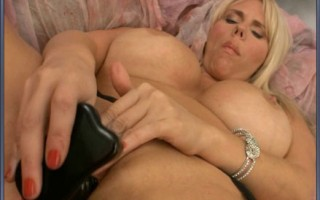 Blonde MILF with big boobies gets herself off with black dildo wearing black garder and stockings