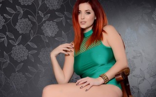Lucy V in green bodysuit on the chair