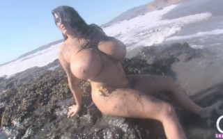 Large boobs babe Leanne Crow at the beach in gold bikini