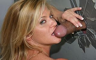 Ginger Lynn gulps a giant black cock in a gloryhole